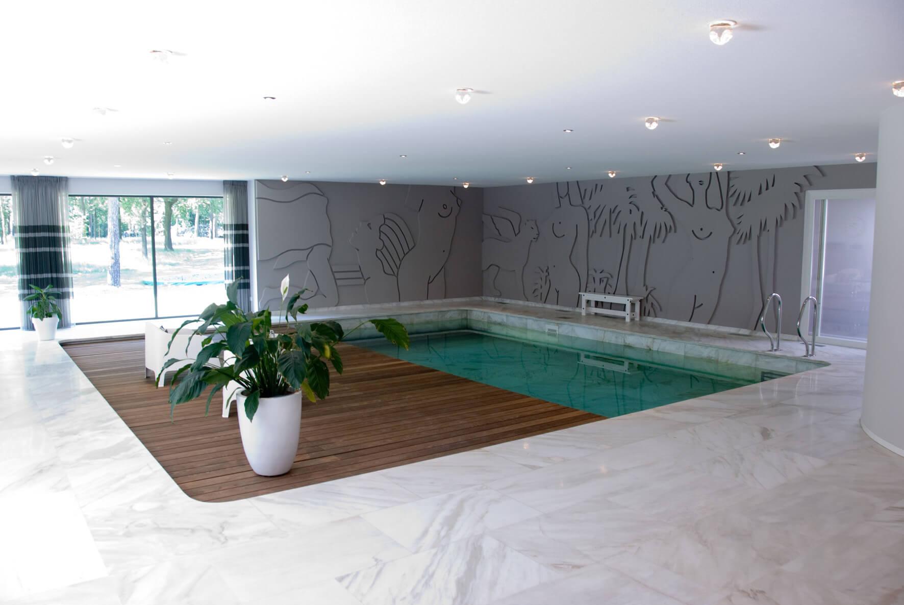 Binnenzwembad met terras en bestaand kunstwerk op wand